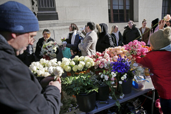 FILE — In this Feb. 14, 2020 file photo, florists prepare bouquets as people wait in a long line to enter the New York City Marriage Bureau, on Valentine's Day. New York City restaurants will be able to reopen for indoor dining at one-quarter capacity by Valentine's Day and big weddings can return statewide in March if infection rates continue to drop, Gov. Andrew Cuomo said Friday, Jan. 29, 2021. (AP Photo/Seth Wenig)