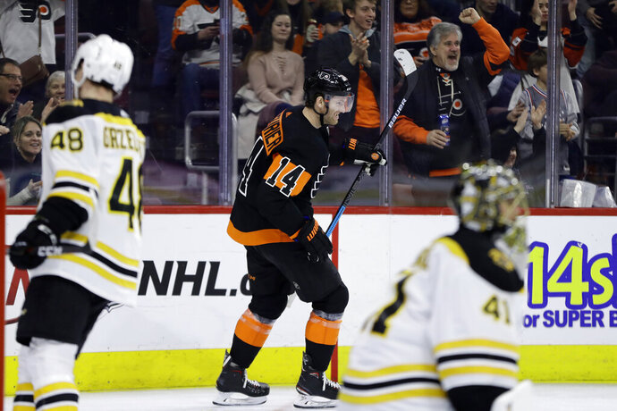 Philadelphia Flyers' Sean Couturier, center, celebrates after scoring a goal past Boston Bruins' Jaroslav Halak, right, and Matt Grzelcyk during the second period of an NHL hockey game, Wednesday, Jan. 16, 2019, in Philadelphia. (AP Photo/Matt Slocum)
