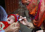 A health worker marks fingers after giving polio vaccinations to child, in Lahore, Pakistan, Monday, Jan. 11, 2021. Despite a steady rise in coronavirus cases, Pakistan on Monday launched a five-day vaccination campaign against polio amid tight security, hoping to eradicate the crippling children's disease this year. (AP Photo/K.M. Chaudary)