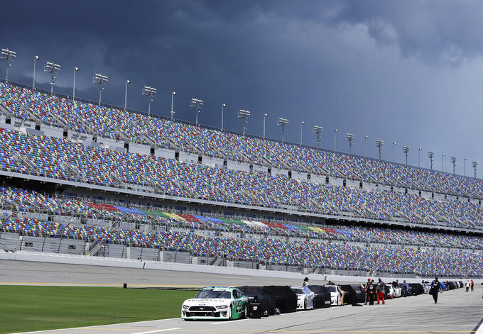 Race cars line pit road as Weather in the area delays the start of the NASCAR Xfinity series auto race at Daytona International Speedway, Saturday, Aug. 15, 2020, in Daytona Beach, Fla. (AP Photo/Terry Renna)