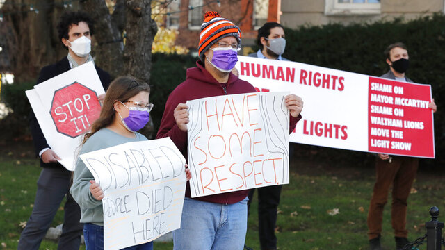 A group protests against a planned holiday event outside the former Walter E. Fernald Developmental Center Friday Nov. 20, 2020, in Waltham, Mass. A plan to create a large drive-thru holiday lights display on the grounds of the disgraced former state facility, where mentally disabled youths once were warehoused and subjected to experiments, has touched off angry protests by activists who say it's inappropriate. (AP Photo/Michael Dwyer)