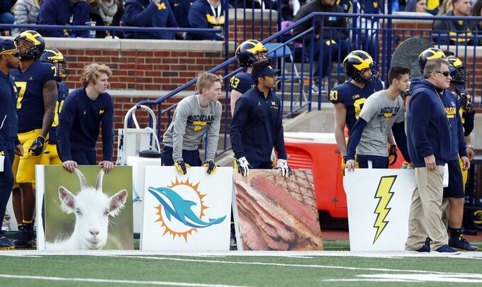 Assistants on the sideline hold formation signs during Michigan's annual spring NCAA college football game, Saturday, April 13, 2019, in Ann Arbor, Mich. (AP Photo/Carlos Osorio)