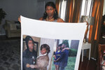 Jennifer McDonald holds a blanket on which is printed photos of her late son, Demontravis Davonte Reid, who was shot and killed in Charlotte, N.C on April 14, 2021. As of July 15, he was among the 56 homicide victims in North Carolina's largest city. Homicide rates in many American cities have continued to rise although not as precipitously as the double-digit jumps seen in 2020 and still below the violence of the mid-90s. (AP Photo/Skip Foreman)