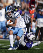 Maine wide receiver Michael Monios (83) gets wrapped up by James Madison safety Wayne Davis (8) during the first half of an NCAA college football game in Harrisonburg, Va., Saturday, Sept. 11, 2021. (Daniel Lin/Daily News-Record via AP)