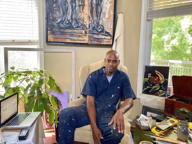 Omari Booker, 39, sits on a chair in his studio Monday, June 15, 2020, in Nashville, Tenn. Booker says his talents were born through a mix of education and life experiences, many of which were rooted in racism and engaging with police as a young Black male. (Damon Mitchell/WPLN-FM via AP)