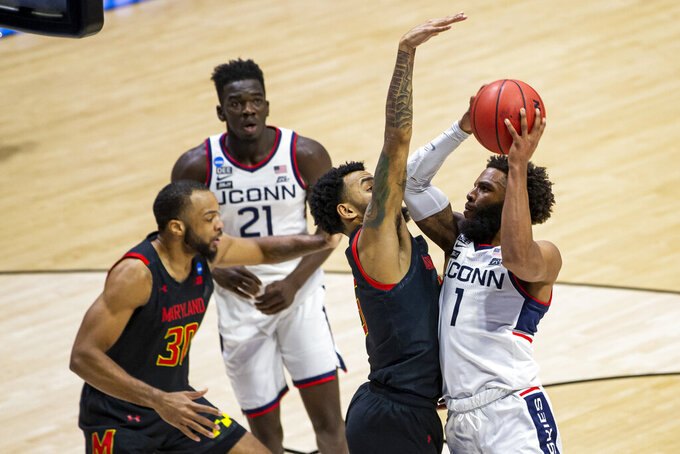 Connecticut's R.J. Cole (1) goes up for a shot as Maryland's Eric Ayala defends during the second half of a first-round game in the NCAA men's college basketball tournament Saturday, March 20, 2021, at Mackey Arena in West Lafayette, Ind. Maryland won 63-54. (AP Photo/Robert Franklin)