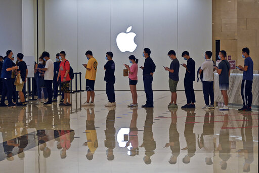 People line up at an Apple Store to buy the latest iPhone 13 handsets in Nanning in south China's Guangxi Zhuang Autonomous Region on Sept. 24, 2021. Global shoppers face possible shortages of smartphones and other goods ahead of Christmas after power cuts to meet government energy use targets forced Chinese factories to shut down and left some households in the dark. (Chinatopix Via AP)
