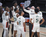 Miami coach Jim Larranaga talks with players as they look up toward the board showing the Hurricanes trailing Purdue during the first half of an NCAA college basketball game Tuesday, Dec. 8, 2020, in Coral Gables, Fla. (Al Diaz/Miami Herald via AP)