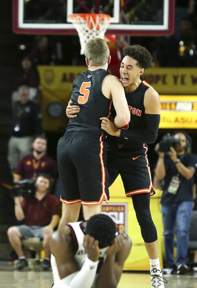 Princeton guard Devin Cannady, right, and teammate Drew Friberg (5) celebrate a victory over Arizona State as Arizona State's Luguentz Dort, bottom, reacts to the loss in an NCAA college basketball game, Saturday, Dec. 29, 2018, in Tempe, Ariz. (AP Photo/Ralph Freso)