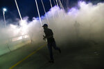 In this Monday, June 1, 2020, photo, a man moves through smoke and tear gas as protesters  marched onto the Margaret Hunt Hill Bridge while demonstrating against police brutality in Dallas. Protests continue over the death of George Floyd, a black man who died after being restrained by Minneapolis police officers on May 25. (Ryan Michalesko/The Dallas Morning News via AP)