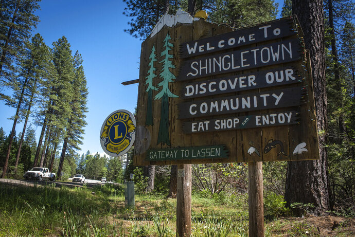 In this photo taken June 11, 2019, is a sign outside Shingletown, Calif. The town got its name from its heyday making wooden roofing materials. The wildfire-vulnerable town has two nicknames, Little Paradise and Gateway to Mount Lassen. Despite federal fire suppression costs quadrupling and an increase in employed firefighters, the damages caused by wildfires has increased fivefold. (Anton L. Delgado/News21 via AP)