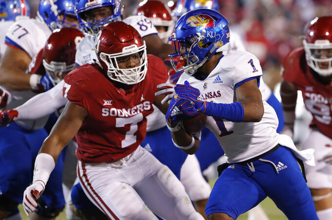 Kansas running back Pooka Williams Jr. (1) runs as Oklahoma defensive end Ronnie Perkins (7) defends during the first half of an NCAA college football game in Norman, Okla., Saturday, Nov. 17, 2018. (AP Photo/Alonzo Adams)
