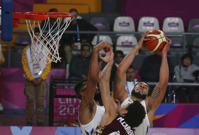 Puerto Rico's Emmanuel Andujar takes a rebound over Venezuela's Michael Carrera during their basketball first round game at the Pan American Games in Lima, Peru, Wednesday, July 31, 2019. (AP Photo/Fernando Llano)