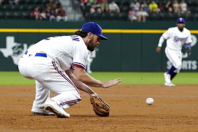 Texas Rangers third baseman Charlie Culberson reaches down to field a grounder by Houston Astros' Chas McCormick, who was out at first during the second inning of a baseball game in Arlington, Texas, Tuesday, Sept. 14, 2021. (AP Photo/Tony Gutierrez)