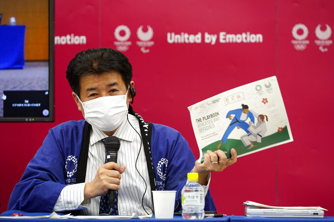 Tokyo 2020 Games Delivery Officer Hidemasa Nakamura holds a sample of the Version Two of Tokyo 2020 Playbook during a press briefing in Tokyo, Japan, 28 April 2021.  The IOC and Tokyo 2020 organizers presented the second version of the playbook saying a third version will be unveiled in the coming weeks. (Franck Robichon / Pool via AP)