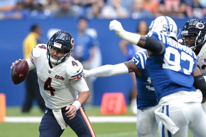 Chicago Bears quarterback Chase Daniel (4) avoids being sacked by Indianapolis Colts' Al-Quadin Muhammad (97) and Kemoko Turay (57) during the first half of an NFL preseason football game Saturday, Aug. 24, 2019, in Indianapolis. (AP Photo/AJ Mast)