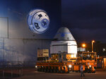 Boeing's Starliner spacecraft is rolled past a mural of itself on the side of the building at the Kennedy Space Center in Cape Canaveral, Fla., before dawn on Thursday, Nov. 21, 2019. The spaceship is scheduled to fly in December. (Malcolm Denemark/Florida Today via AP)