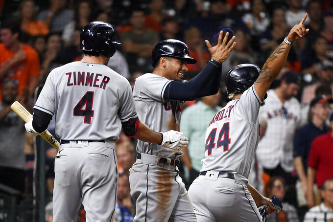 Cleveland Indians' Oscar Mercado, center, celebrates, after scoring a run on Ernie Clement's three-run double, with Bradley Zimmer (4) and Bobby Bradley during the sixth inning of the team's baseball game against the Houston Astros, Wednesday, July 21, 2021, in Houston. (AP Photo/Eric Christian Smith)