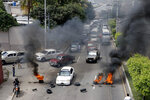 Demonstrators block a street, demanding the resignation of President Juan Orlando Hernandez, in Tegucigalpa, Honduras , Thursday, Oct. 24 2019. Calls for President Hernandez's resignation came after his younger brother was convicted on drug trafficking charges in New York and testimony implicated the president in his drug enterprise. (AP Photo/Elmer Martinez)