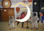 An employee playfully hugs a cut-out of a crescent moon at the Nehru Planetarium in New Delhi, India, Thursday, July 11, 2019. India is looking to take a giant leap in its space program and solidify its place among the world's spacefaring nations with its second unmanned mission to the moon, this one aimed at landing a rover near the unexplored south pole. (AP Photo/Altaf Qadri)
