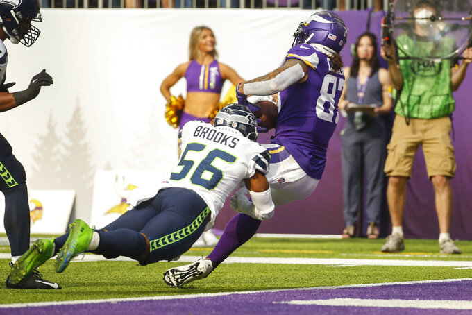 Minnesota Vikings tight end Tyler Conklin (83) scores a touchdown as he's hit by Seattle Seahawks linebacker Jordyn Brooks (56) in the first half of an NFL football game in Minneapolis, Sunday, Sept. 26, 2021. (AP Photo/Bruce Kluckhohn)