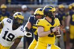 Michigan defensive lineman Kwity Paye (19) rushes quarterback Shea Patterson during the team's annual spring NCAA college football game, Saturday, April 13, 2019, in Ann Arbor, Mich. (AP Photo/Carlos Osorio)