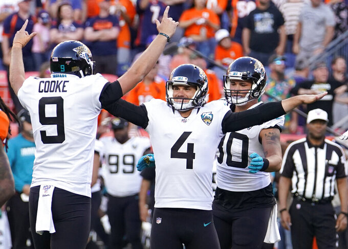 Jacksonville Jaguars kicker Josh Lambo (4) celebrates with teammate holder Logan Cooke (9) after making a game-winning field goal during the second half of an NFL football game against the Denver Broncos, Sunday, Sept. 29, 2019, in Denver. (AP Photo/Jack Dempsey)