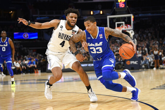 Seton Hall guard Shavar Reynolds (33) dribbles the ball next to Georgetown guard Jagan Mosely (4) during the first half of an NCAA college basketball game, Wednesday, Feb. 5, 2020, in Washington. (AP Photo/Nick Wass)