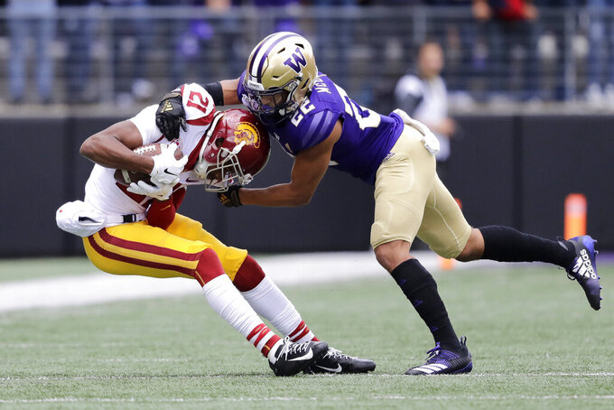 Southern Cal's Tyler Vaughns, left, is tackled by Washington's Trent McDuffie, right, in the first half of an NCAA college football game Saturday, Sept. 28, 2019, in Seattle. (AP Photo/Elaine Thompson)