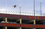 In this May 21, 2019 photo, a drone flies over downtown Reno, Nev., before landing on the Cal-Neva casino parking garage, as part of a NASA simulation to test emerging technology that someday will be used to manage travel of hundreds of thousands of commercial, unmanned aerial vehicles (UAVs) delivering packages. It marked the first time such tests have been conducted in an urban setting. (AP Photo/Scott Sonner)