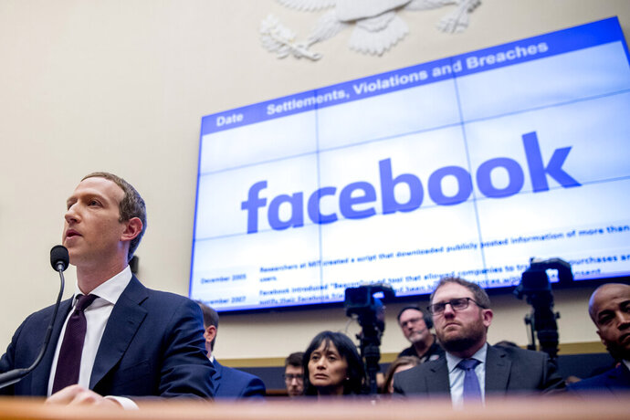 """File-This Oct. 23, 2019, file photo shows Facebook CEO Mark Zuckerberg testifying  before a House Financial Services Committee hearing on Capitol Hill in Washington. Facebook's stock dropped almost 3% in regular trading after news reports Thursday, Dec. 12, 2019, suggested that the FTC may take antitrust action to prevent Facebook from integrating its disparate messaging apps. The reports said the Federal Trade Commission may seek a court injunction that would block Facebook's """"interoperability"""" plans for Facebook Messenger, WhatsApp and Instagram, which involves revising them to use the same underlying software. (AP Photo/Andrew Harnik, File)"""