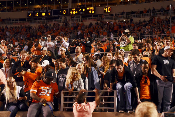 Oklahoma State fans jump down from the stadium wall to take the field following an NCAA college football game against Texas, in Stillwater, Okla., Saturday, Oct. 27, 2018. Oklahoma State defeated Texas 38-35. (AP Photo/Brody Schmidt)
