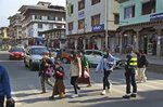 Bhutanese people wearing face masks as precaution against coronavirus cross a street in Thimpu, Bhutan, Monday, April 12, 2021. The tiny Himalayan kingdom wedged between India and China has vaccinated nearly 93% of its adult population since March 27. Overall, the country has vaccinated 62% of its 800,000 people. (AP Photo)