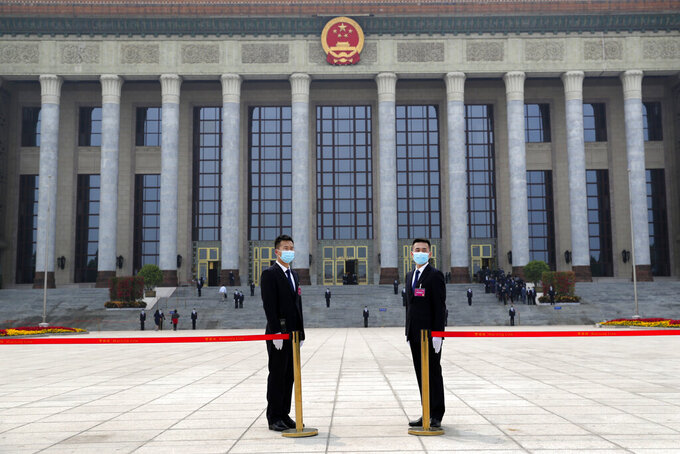 Security officers wearing face masks to protect against the spread of the new coronavirus stand guard outside the Great Hall of the People before the opening session of the Chinese People's Political Consultative Conference (CPPCC) in Beijing, Thursday, May 21, 2020. (AP Photo/Andy Wong, Pool)