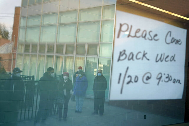 People waiting in line are reflected in the glass windows of a vaccination site in Paterson, N.J., Tuesday, Jan. 19, 2021. A sign on the door of the vaccination site, which takes walk-ins rather than appointments, said it would be open the following day on Wednesday. (AP Photo/Seth Wenig)