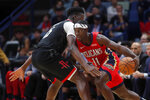 New Orleans Pelicans guard Jrue Holiday (11) drives to the basket against Houston Rockets center Clint Capela in the first half of an NBA basketball game in New Orleans, Monday, Nov. 11, 2019. (AP Photo/Gerald Herbert)