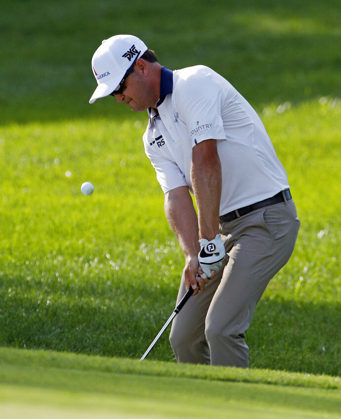 Zach Johnson chips to the 15th green during the first round of the PGA Championship golf tournament at Bellerive Country Club, Thursday, Aug. 9, 2018, in St. Louis. (AP Photo/Charlie Riedel)