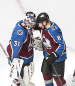 Colorado Avalanche goalie Philipp Grubauer (31) and teammate Cale Makar (8) celebrate the team's win over the Arizona Coyotes in Game 1 of an NHL hockey Stanley Cup first-round playoff series, Wednesday, Aug. 12, 2020, in Edmonton, Alberta. (Jason Franson/The Canadian Press via AP)