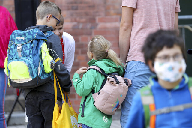 Students are brought to school by their parents in Rostock, Germany Monday, Aug. 3, 2020 as Mecklenburg-Western Pomerania is the first federal state to resume regular school operations throughout the state. About 150,000 students are expected to attend their schools. (Bernd W'stneck/dpa-Zentralbild/dpa via AP)