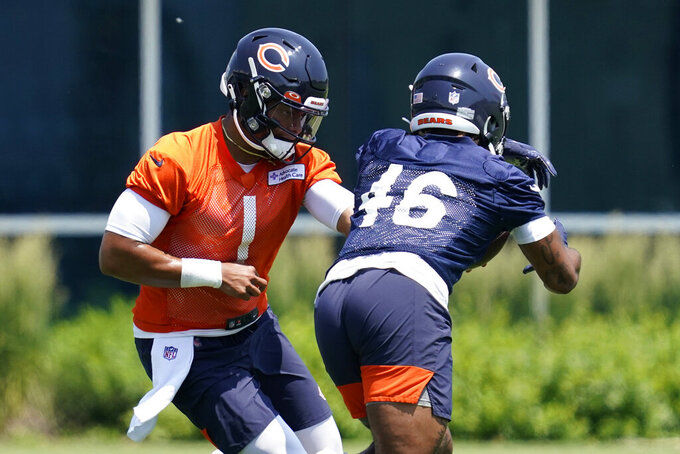 Chicago Bears quarterback Justin Fields, left, hands off the ball to running back Artavis Pierce during NFL football practice in Lake Forest, Ill., Wednesday, June 9, 2021. (AP Photo/Nam Y. Huh)