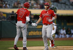 Los Angeles Angels' Mike Trout, right, is congratulated by Shohei Ohtani (17) after hitting a home run off Oakland Athletics pitcher Mike Fiers during the first inning of a baseball game Tuesday, Sept. 3, 2019, in Oakland, Calif. (AP Photo/Ben Margot)