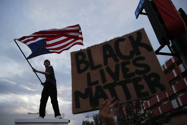 Protesters rally Saturday, May 30, 2020, in Las Vegas, over the death of George Floyd, a black man who was in police custody in Minneapolis. Floyd died after being restrained by Minneapolis police officers on Memorial Day. (AP Photo/John Locher)