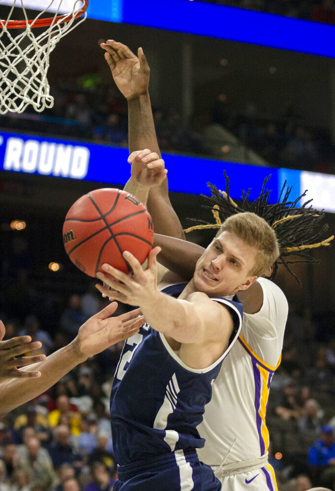 Yale forward Blake Reynolds (32) goes after a rebound against LSU forward Naz Reid, rear, during the second half of the first round men's college basketball game in the NCAA Tournament in Jacksonville, Fla., Thursday, March 21, 2019. (AP Photo/Stephen B. Morton)