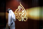 FILE - In this Nov. 1, 2006 file photo, a Qatari employee of Al-Jazeera Arabic language TV news channel walks past the logo of Al-Jazeera in Doha, Qatar. An Egyptian court on Thursday, May 23, 2019, ordered the release of an Al-Jazeera journalist who had been detained since 2016 on allegations of spreading false news and defaming Egypt's reputation. Mahmoud Hussein, an Egyptian journalist working for the Qatar-based satellite network, was detained at the Cairo airport in December 2016 when he arrived on a family vacation from Doha. No official charges were ever raised against him and Hussein didn't stand trial.   (AP Photo/Kamran Jebreili, File)