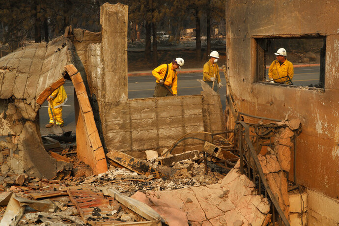 Fire crews clear rubble from the road near a building burned in the Camp Fire, Monday, Nov. 12, 2018, in Paradise, Calif. (AP Photo/John Locher)