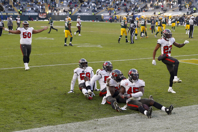 Tampa Bay Buccaneers celebrate after recovering a fumble by Green Bay Packers' Aaron Jones (33) after being hit by Tampa Bay Buccaneers' Jordan Whitehead (33) during the second half of the NFC championship NFL football game in Green Bay, Wis., Sunday, Jan. 24, 2021. (AP Photo/Mike Roemer)