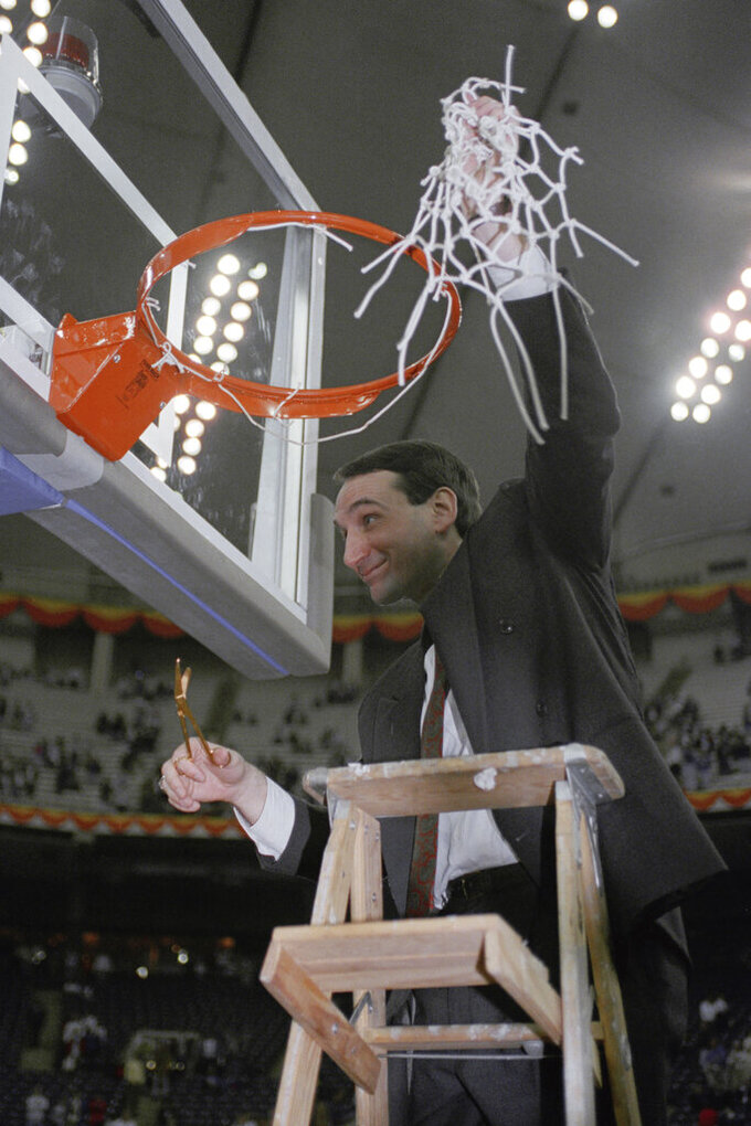 FILE - In this April 2, 1991, file photo, Duke coach Mike Krzyzewski finishes the traditional net cutting in the Indianapolis Hoosier Dome after Duke defeated Kansas 72-65 in the NCAA Final Four championship game. Recouping from a 30-point loss in last year's NCAA championship game, Duke beat top-ranked UNLV and then Kansas to win the championship for the first time. (AP Photo/Bob Jordan, File)
