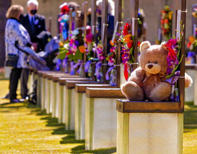 Flowers and gifts decorate the memorial chairs in the Field of Chairs for the 26th Anniversary Remembrance Ceremony at the Oklahoma City National Memorial and Museum in Oklahoma City, Okla on Monday, April 19, 2021. (Chris Landsberger/The Oklahoman via AP)