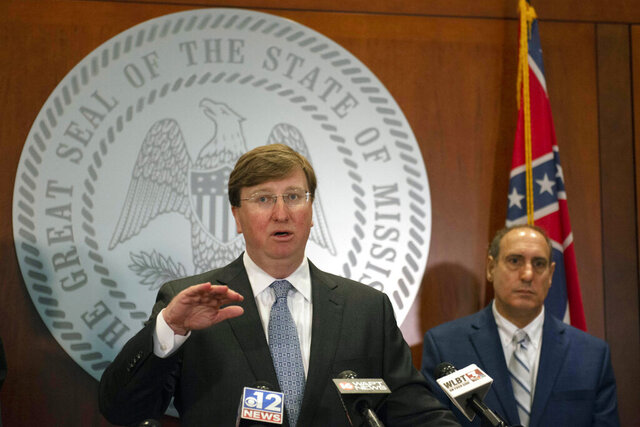 Mississippi Gov. Tate Reeves, left, speaks at a press conference on Tuesday morning, March 31, 2020, in Jackson, Miss., as state epidemiologist Dr. Paul Byers, right, listens. Reeves signed a new executive order establishing a shelter-in-place for Lauderdale County, effective through April 14, 2020. (Sarah Warnock/The Clarion-Ledger via AP)