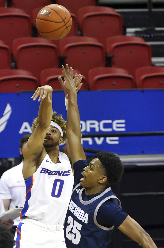 Boise State guard Marcus Shaver Jr. (0) shoots as Nevada guard Grant Sherfield (25) defends during the second half of an NCAA college basketball game in the quarterfinals of the Mountain West Conference men's tournament Thursday, March 11, 2021, in Las Vegas. (AP Photo/Isaac Brekken)